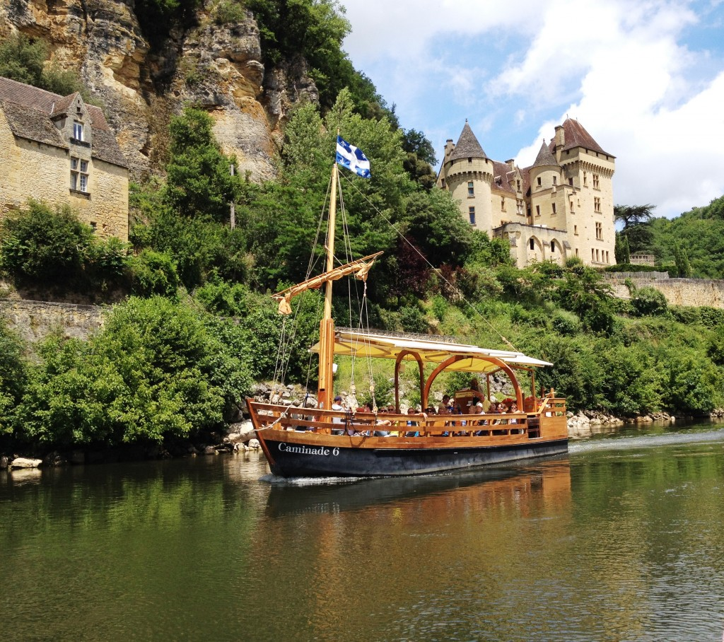 The town of La Roque-Gageac and a traditional gabare boat.
