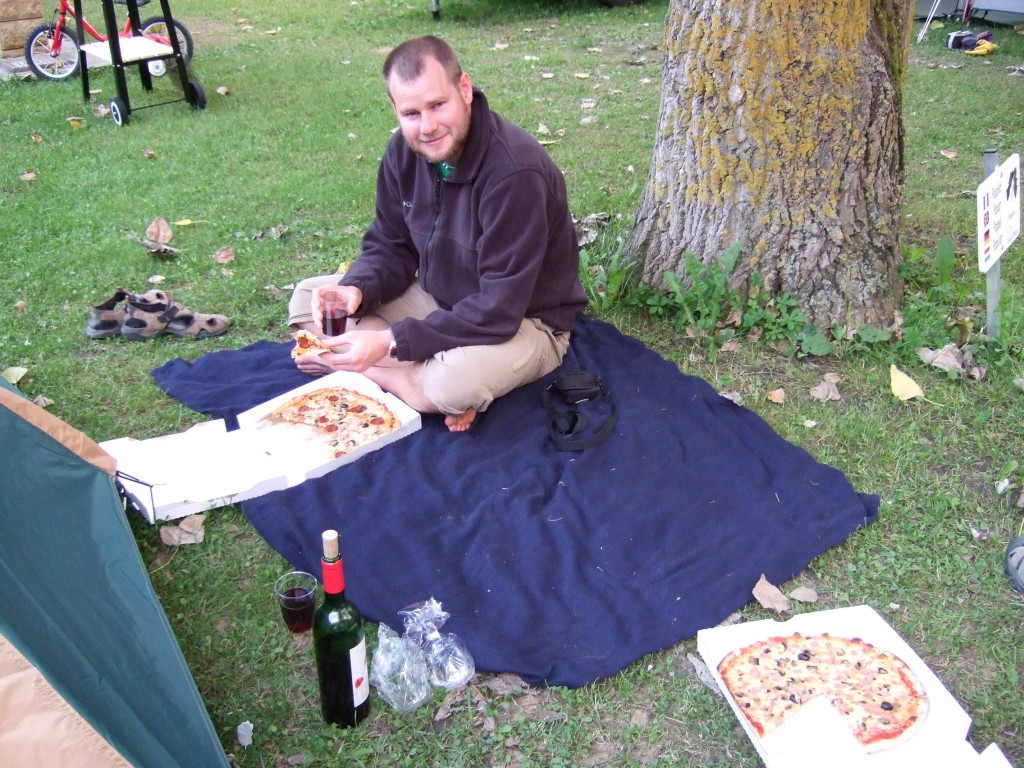 Camping takeaway styles with a pizza and bottle of vin rouge.
